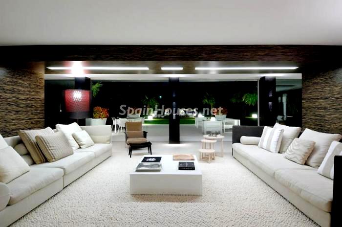 Salón minimalista, vistas a los jardines y la piscina de la casa