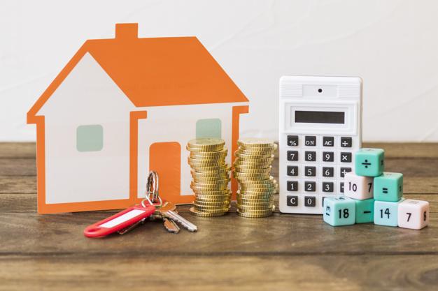 casa llave monedas apiladas calculadora bloques matematicas mesa madera 23 2147863938 - ¿Cuáles son los gastos en el alquiler de un piso?
