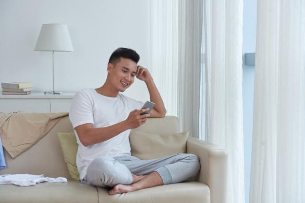 chico alegre disfrutando su tiempo libre mirando redes sociales sentado comodamente sofa 1098 19238 - Lofts de solteros que amarás para vivir