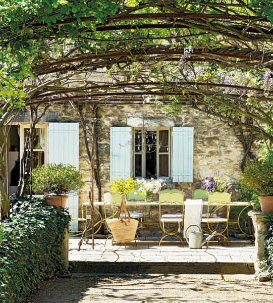 comedor exterior con mesa y sillas de hierro antiguas 1155x1280 541x600 - La Ferme du Bon Dieu: Una granja convertida en casa que alberga una historia de amor