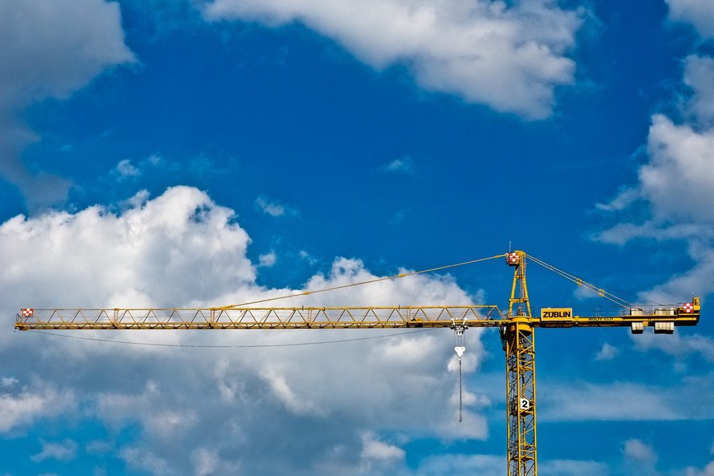 Grúa recortada contra el cielo y las nubes, metáfora de la situación de la construcción en España