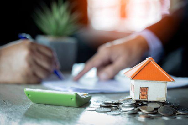 empresario firma contrato detras de modelo arquitectonico de casa 2379 1670 1 600x400 - ¿Puedo vender una casa con la hipoteca pendiente de pagar?