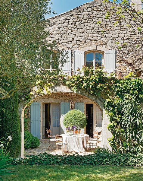 fachada de piedra de casa rustica con mesa y sillas junto al arco 1013x1280 475x600 - La Ferme du Bon Dieu: Una granja convertida en casa que alberga una historia de amor