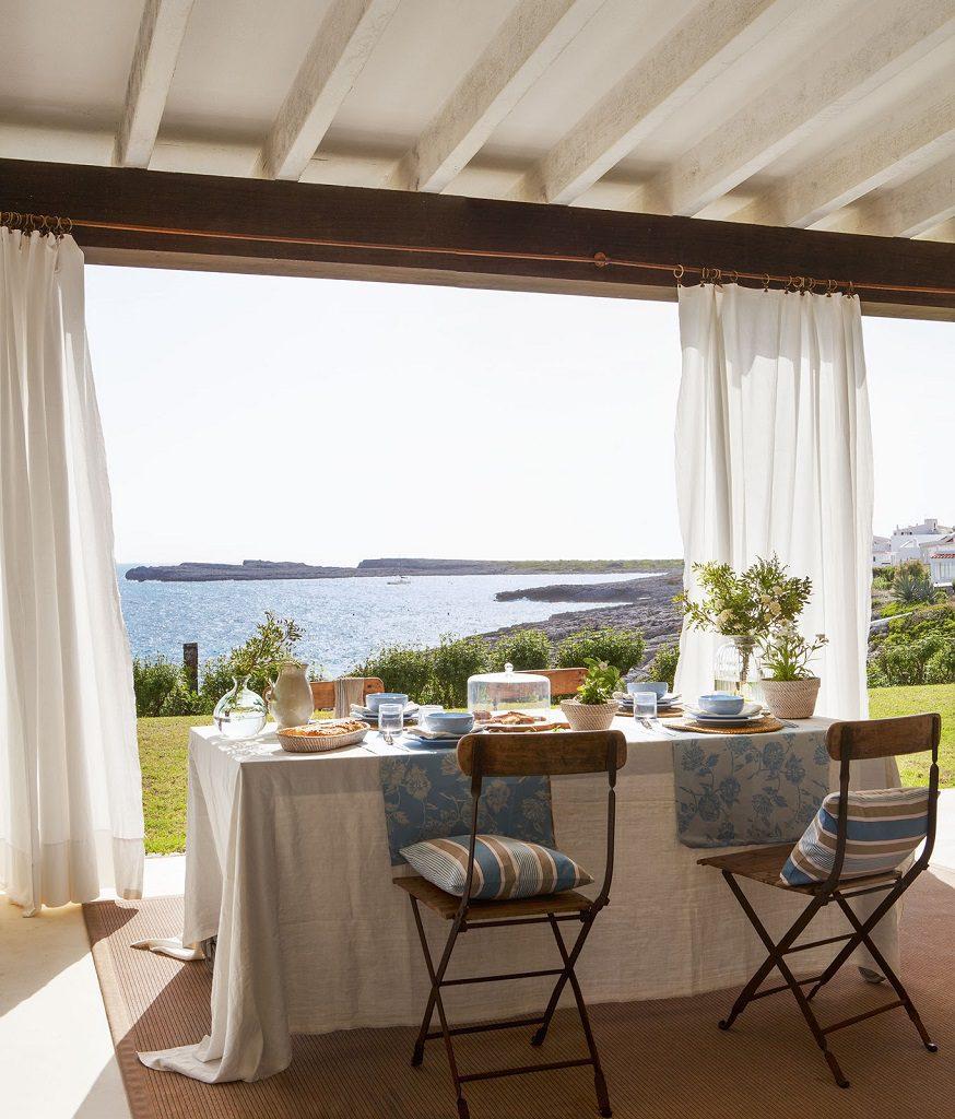 porche mesa vistas 874x1024 - Fantástica casa junto al mar en Menorca (Baleares) abierta al Mediterráneo