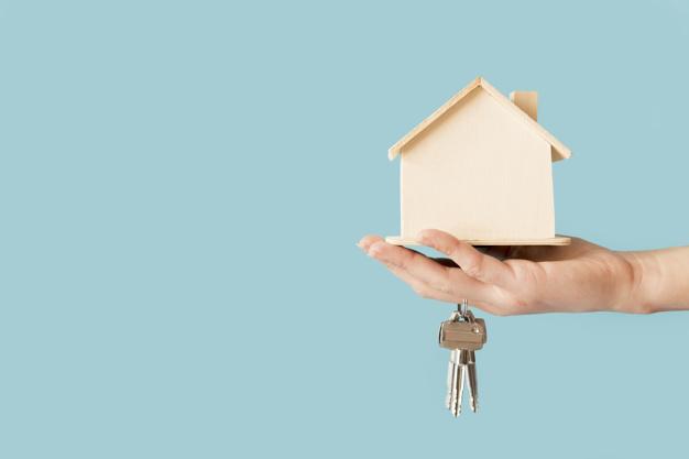 primer plano mano que sostiene llaves modelo casa madera contra fondo azul 23 2148038680 1 - ¿Qué es una vivienda de protección oficial? ¿Puedo acceder a ella?